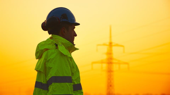 Man in a fluorescent jacket and safety hat near electricity pylons at sunset