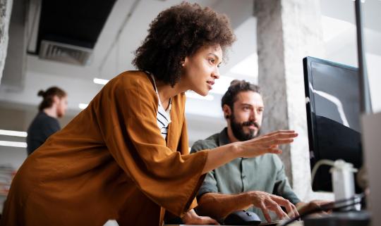 A man and a woman collaborating at a computer screen