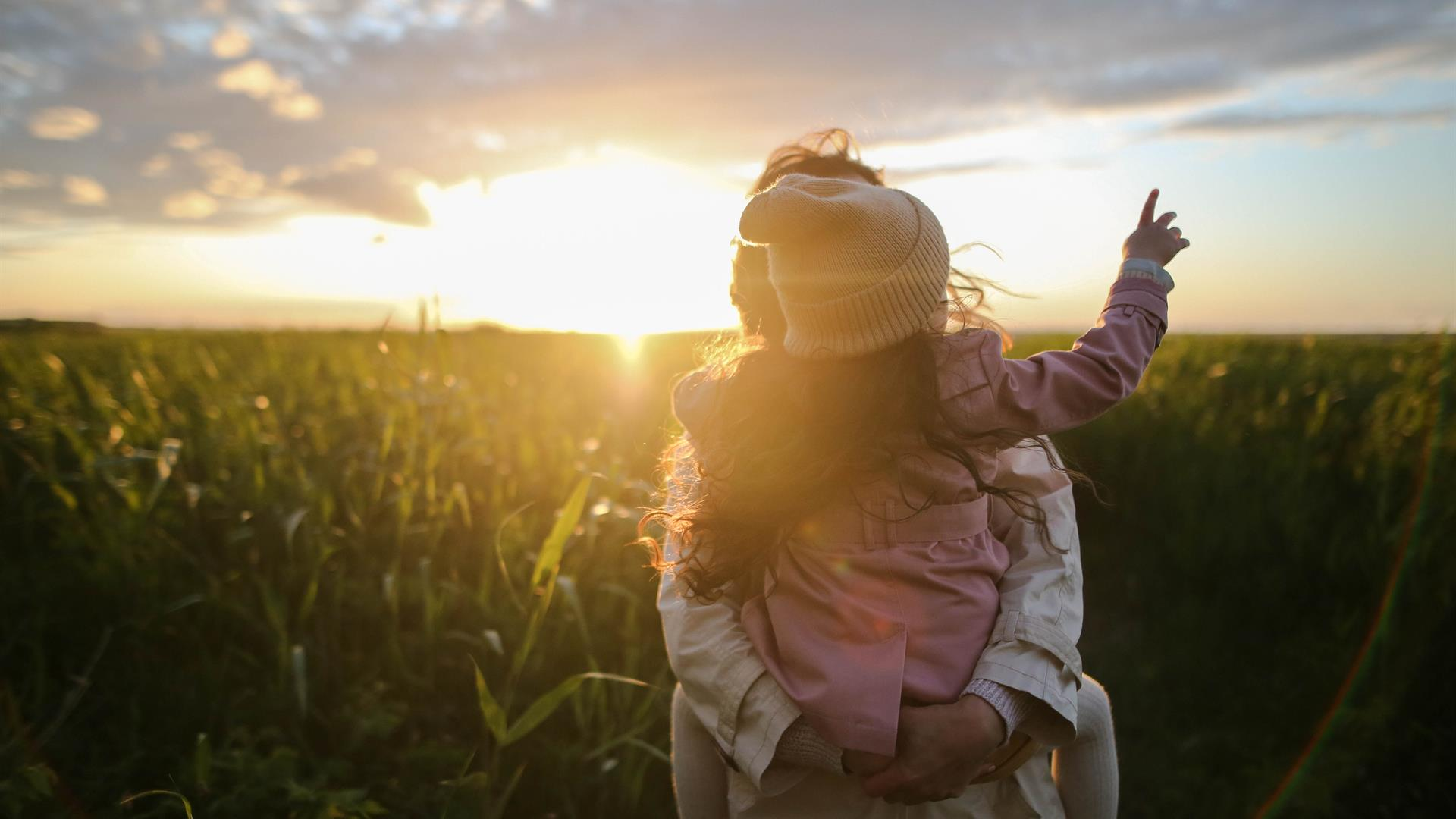 A mother and daughter standing in a field at sunset
