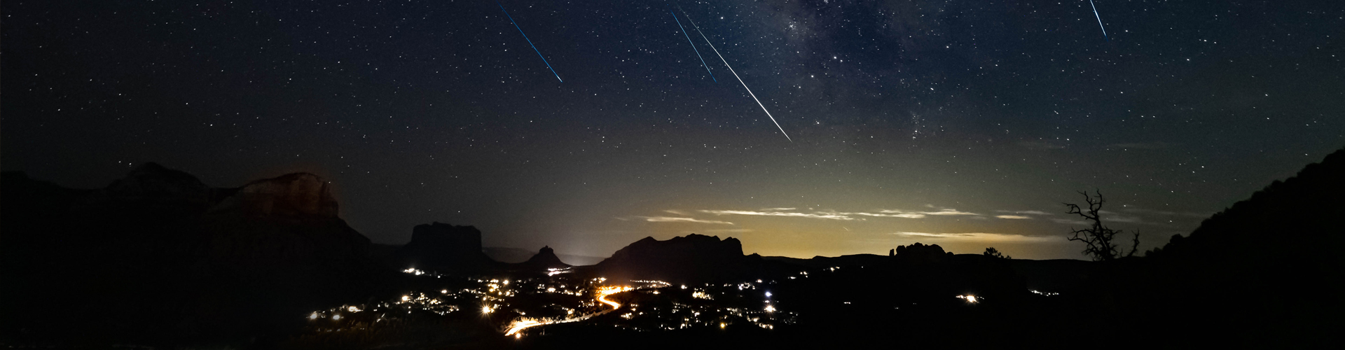 Silhouette of town at night with shooting stars in the sky